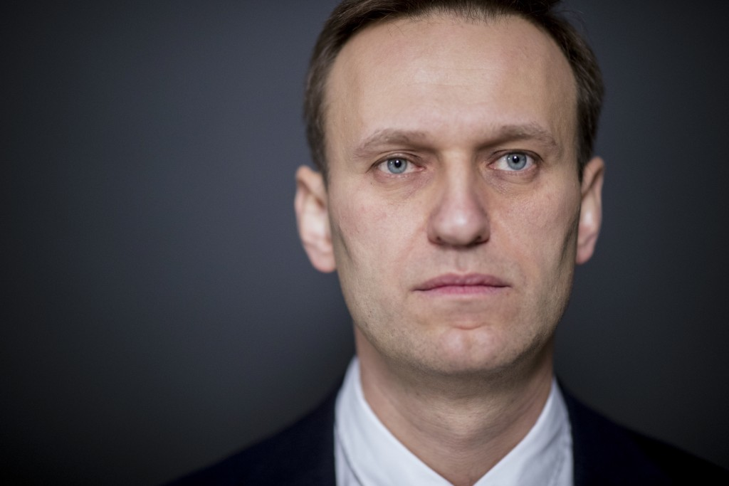 Russian opposition leader Alexei Navalny, who submitted endorsement papers necessary for his registration as a presidential candidate, center, listens...