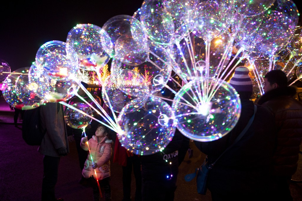 In this Dec. 25, 2017, file photo, a child chooses from LED embedded balloons on sale at a shopping district in Beijing, China. (AP Photo/Ng Han Guan,...