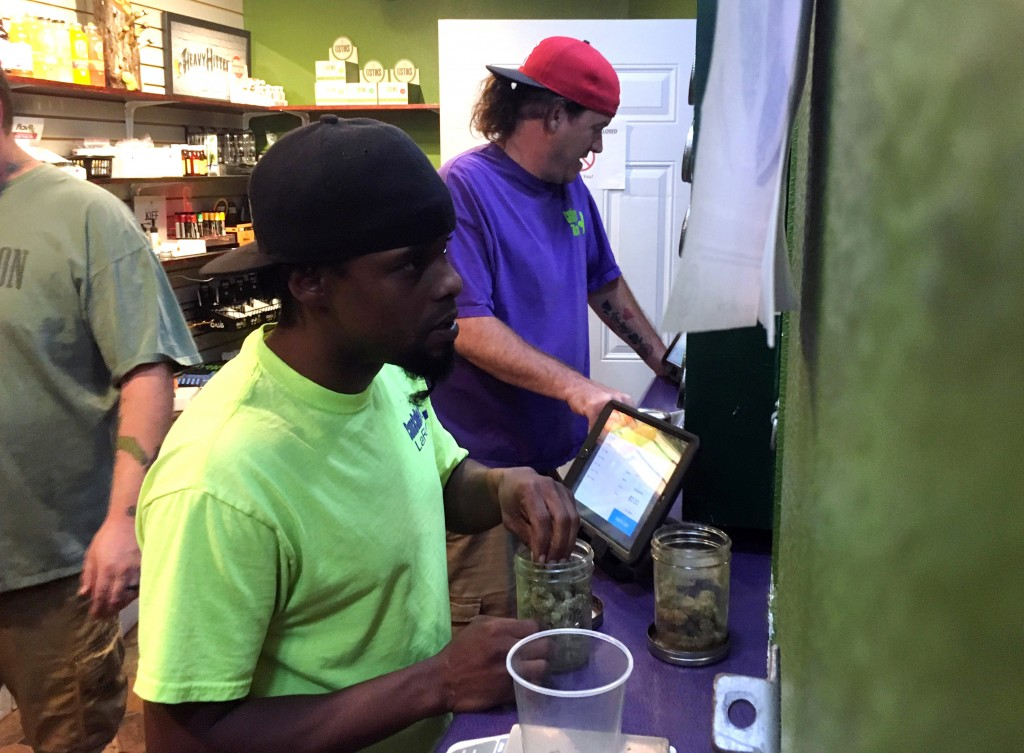 In this Tuesday, Oct. 3, 2017, photo, Thomas Grier, right, and LaRoy Washington work at Canna Can Help Inc., a medical marijuana dispensary in Goshen,...