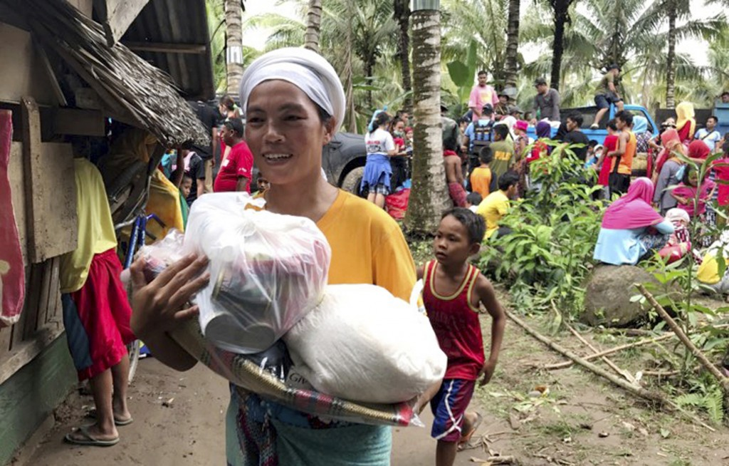 A resident smiles as she walks home with relief supplies being distributed to storm-affected villages of Lanao del Norte Sunday, Dec. 24, 2017 in sout...