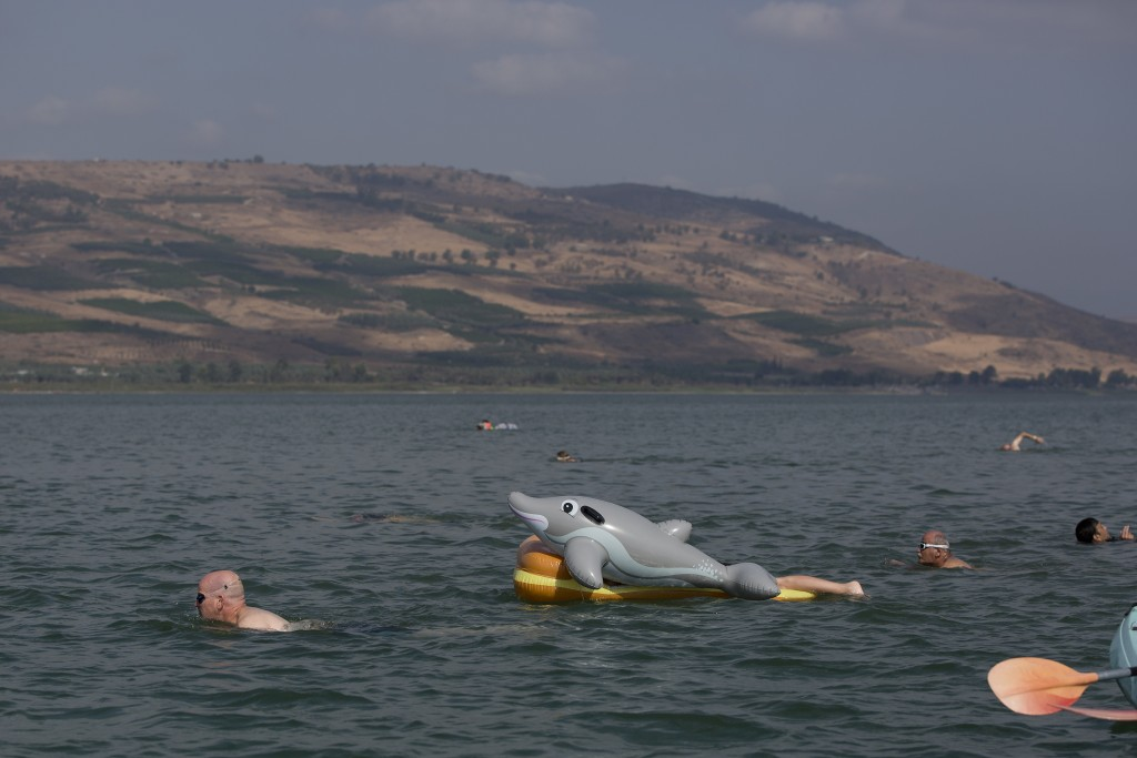 FILE- in this Saturday, Sept. 16, 2017, file photo, swimmers participate in the annual Sea of Galilee swim, the oldest and most popular swimming event...
