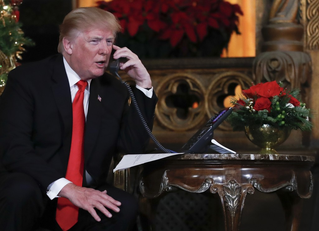 President Donald Trump speaks on the phone with children as they track Santa Claus' movements with the North American Aerospace Defense Command (NORAD...