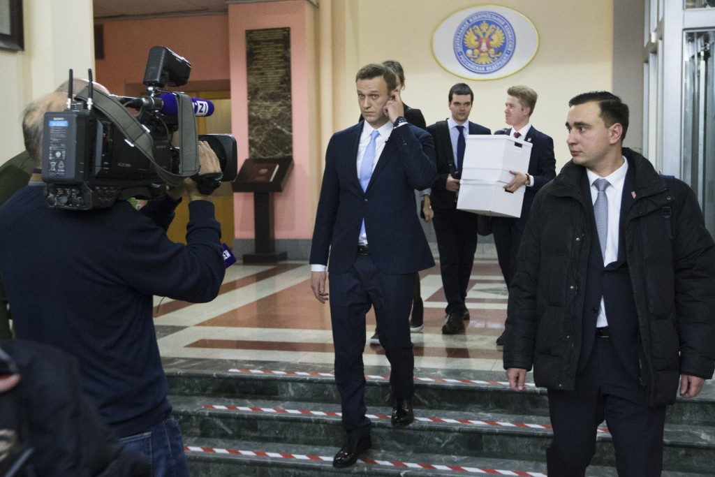 Russian opposition leader Alexei Navalny, center, leaves the Russia's Central Election commission in Moscow, Russia, Sunday, Dec. 24, 2017. The 41-yea...