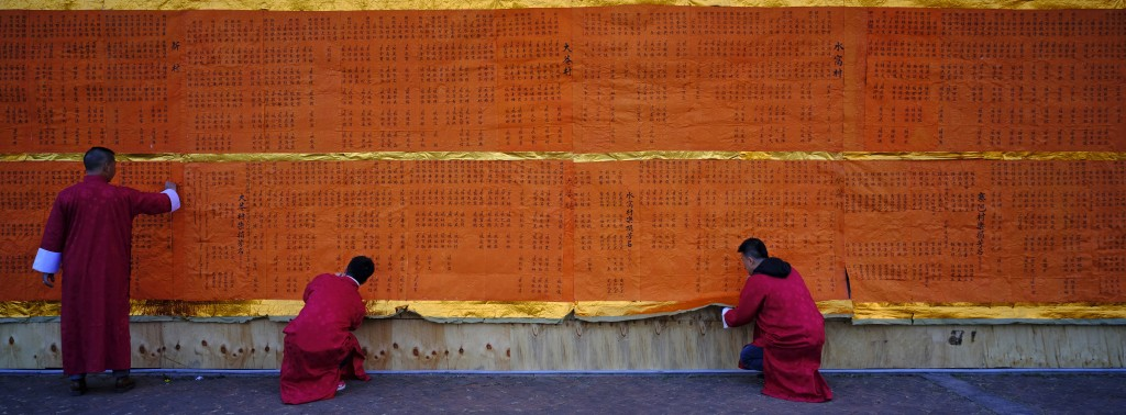 In this Dec. 10, 2017, photo, villagers try to take off a huge donation list to burn during the Tai Ping Ching Jiu festival at Lam Tsuen village in Ho...
