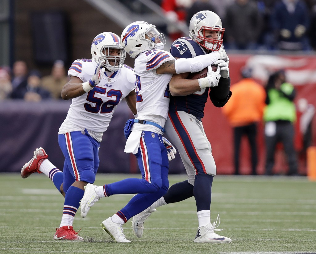 Buffalo Bills safety Jordan Poyer, center, tackles New England Patriots tight end Rob Gronkowski, right, after he caught a pass during the second half...