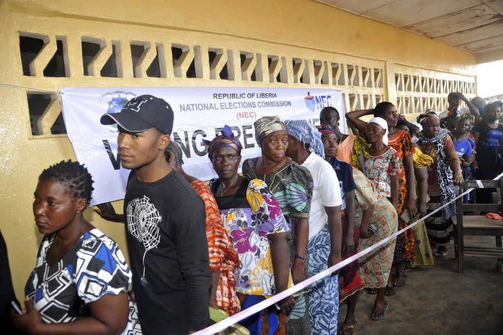 FILE - In this Oct. 10, 2017, file photo, people wait to cast their votes during a Presidential election in Monrovia, Liberia. Liberians head to the p...