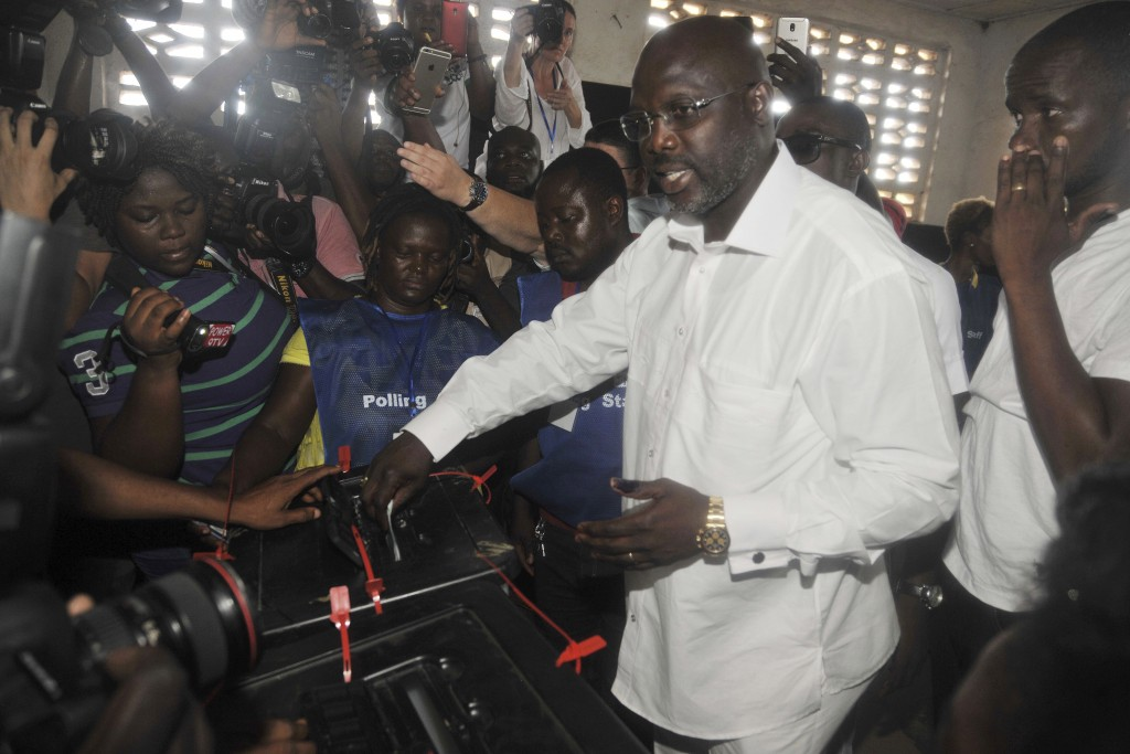 FILE - In this Oct. 10, 2017, file photo, former soccer star George Weah, presidential candidate for the Coalition for Democratic Change, casts his vo...