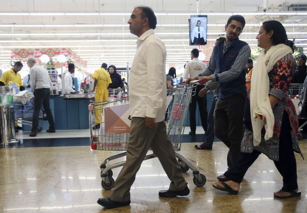 In this Wednesday, Dec. 20, 2017 photo, people leave a hypermarket at a shopping mall in Dubai, United Arab Emirates. Residents in the traditionally t...