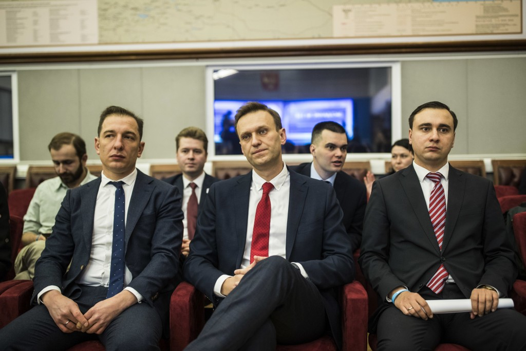 Russian opposition leader Alexei Navalny, who submitted endorsement papers necessary for his registration as a presidential candidate, center, sits at...