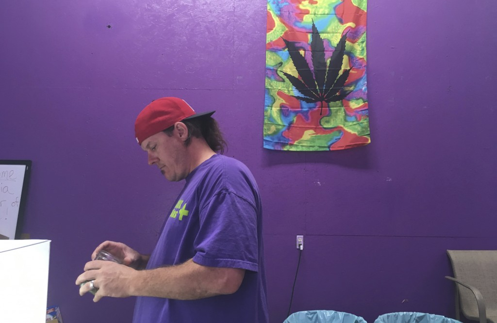 """In this Tuesday, Oct. 3, 2017, photo, Thomas Grier works as a """"bud tender"""" at Canna Can Help Inc., a medical marijuana dispensary in Goshen, Calif. La..."""