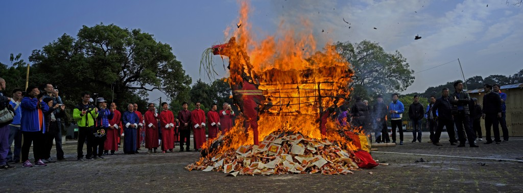 In this Dec. 10, 2017 photo, villagers watch a paper horse burn during a ceremony they hope will bring them luck at the Tai Ping Ching Jiu festival at...