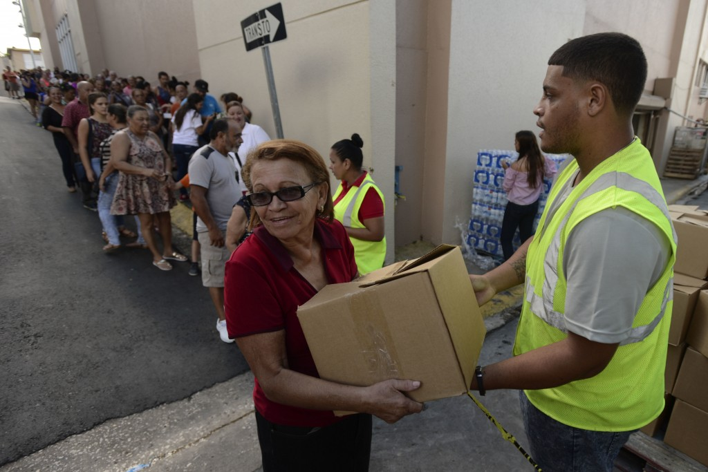 In this Dec. 21, 2017 photo, Doris Martínez receives supplies and water from municipal staff outside the City Hall in Morovis, Puerto Rico. Over 30,00...