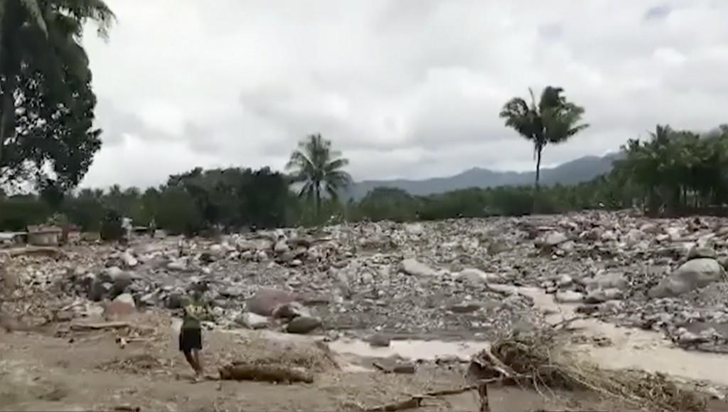 In this image made from video taken Dec. 24, 2017, people stand in the area damaged by storm Tembin in Lanao del Norte, southern Philippines. Thousand...