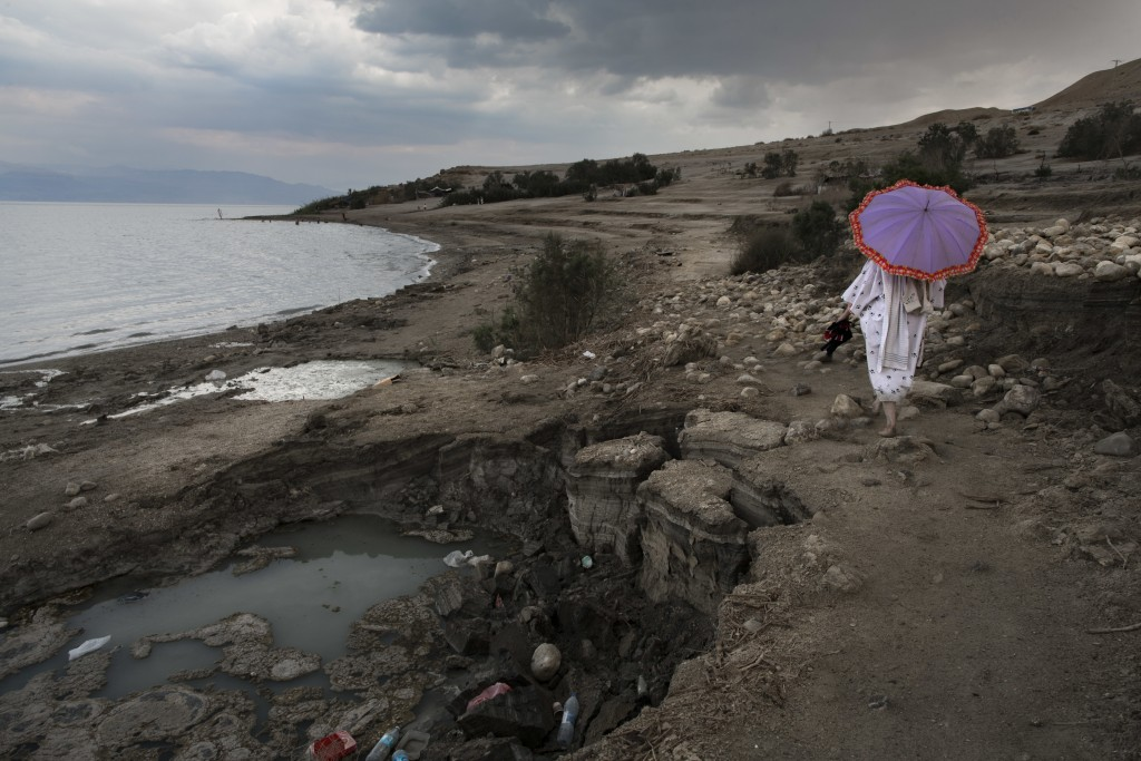 In this April 2, 2017 photo, a woman walks next to sinkholes along the Dead Sea shore near the Israeli Kibbutz of Ein Gedi. The Dead Sea, a marvel of ...