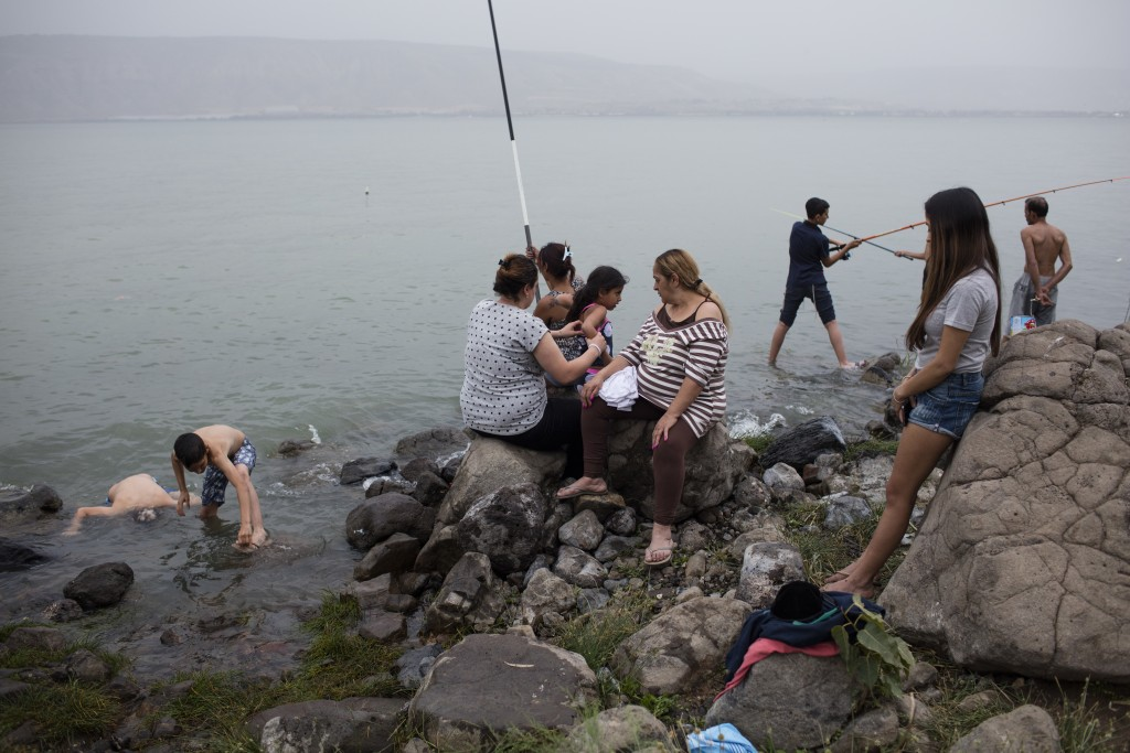 In this Wednesday, April. 12, 2017 photo, Israelis fish in the Sea of Galilee during the Jewish holiday of Passover, near the northern Israeli town of...
