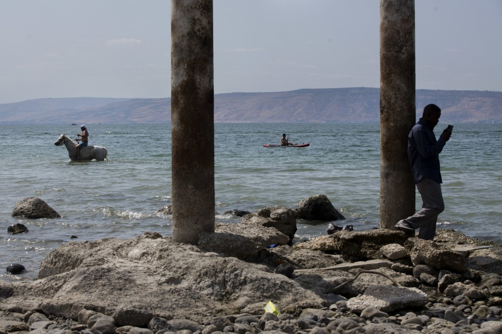 In this Sept. 23, 2017 photo, people enjoy the Sea of Galilee near the northern Israeli Kibbutz of Ein Gev. Israel is heading into its fifth consecuti...