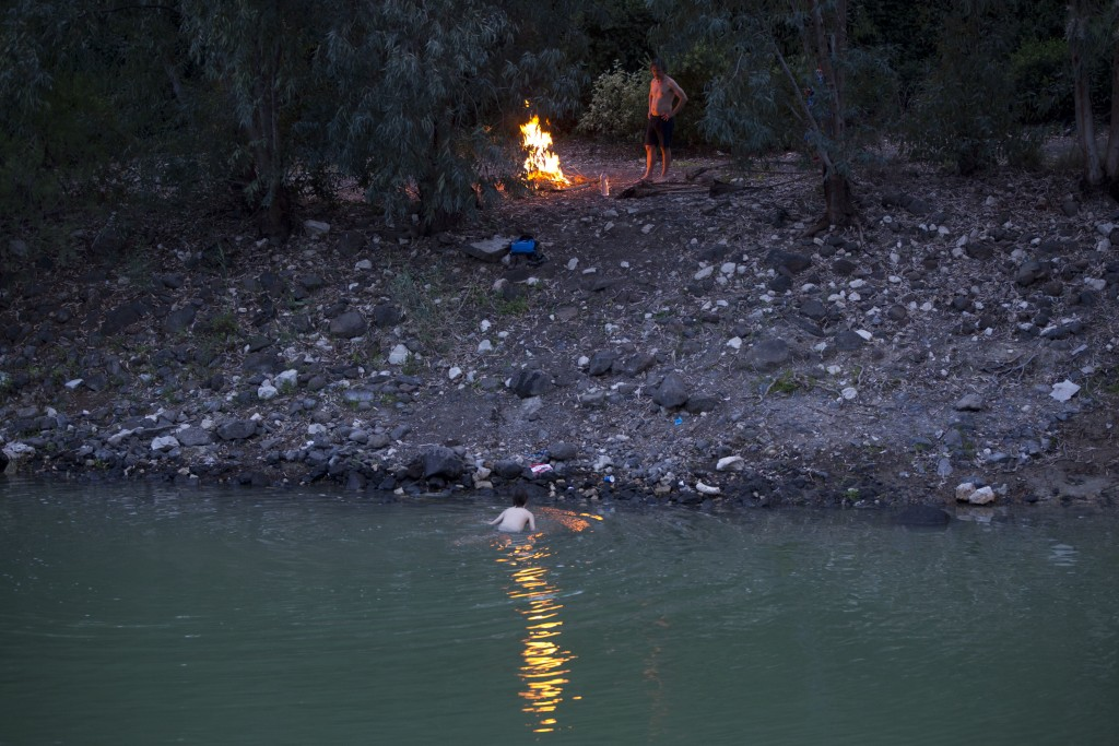 In this Tuesday, April. 11, 2017 photo, Israelis camp out on the banks of the Jordan River near the northern Israeli Kibbutz of Kinneret. Israel is he...