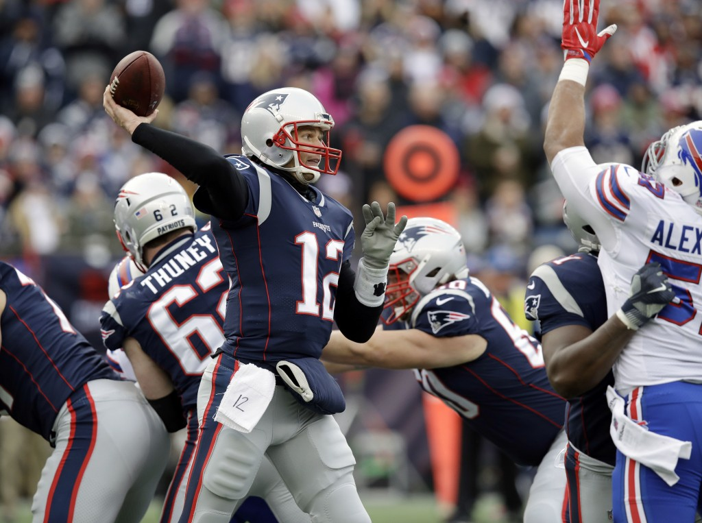 New England Patriots quarterback Tom Brady (12) passes against the rush of Buffalo Bills linebacker Lorenzo Alexander (57) during the first half of an...