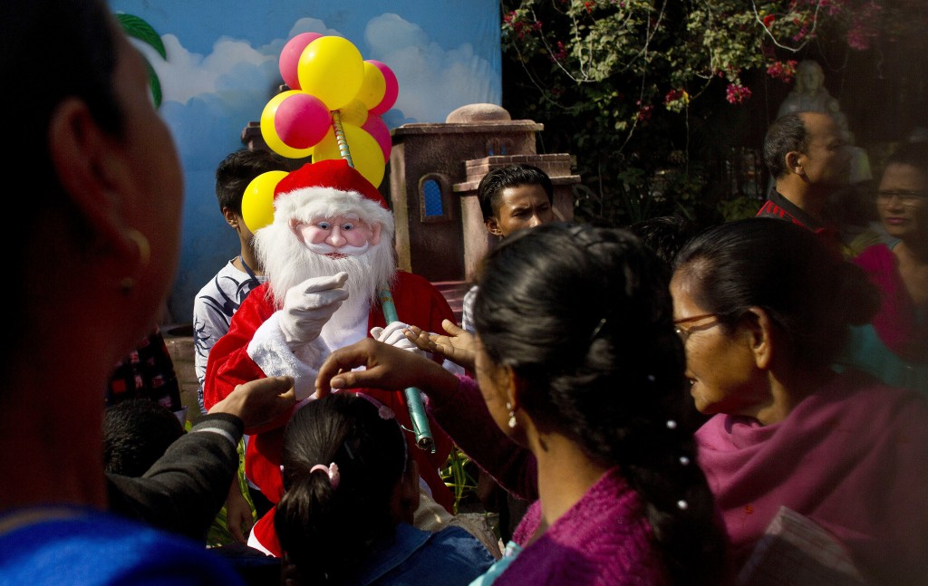 A man dressed as Santa Claus distributes sweets to the devotees after the Christmas prayers at a Church in Gauhati, India, Monday, Dec. 25, 2017. Thou...