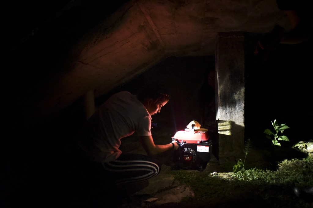 In this Dec. 21, 2017 photo, barrio Patron resident Karina Santiago Gonzalez works on a small power plant in Morovis, Puerto Rico. More than three mon...