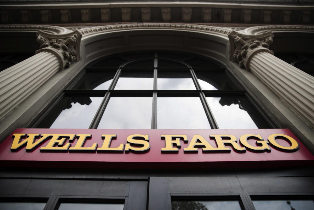 FILE - This Friday, Aug. 11, 2017, file photo shows a sign at a Wells Fargo bank location in Philadelphia. Wells Fargo stands to benefit from the new ...