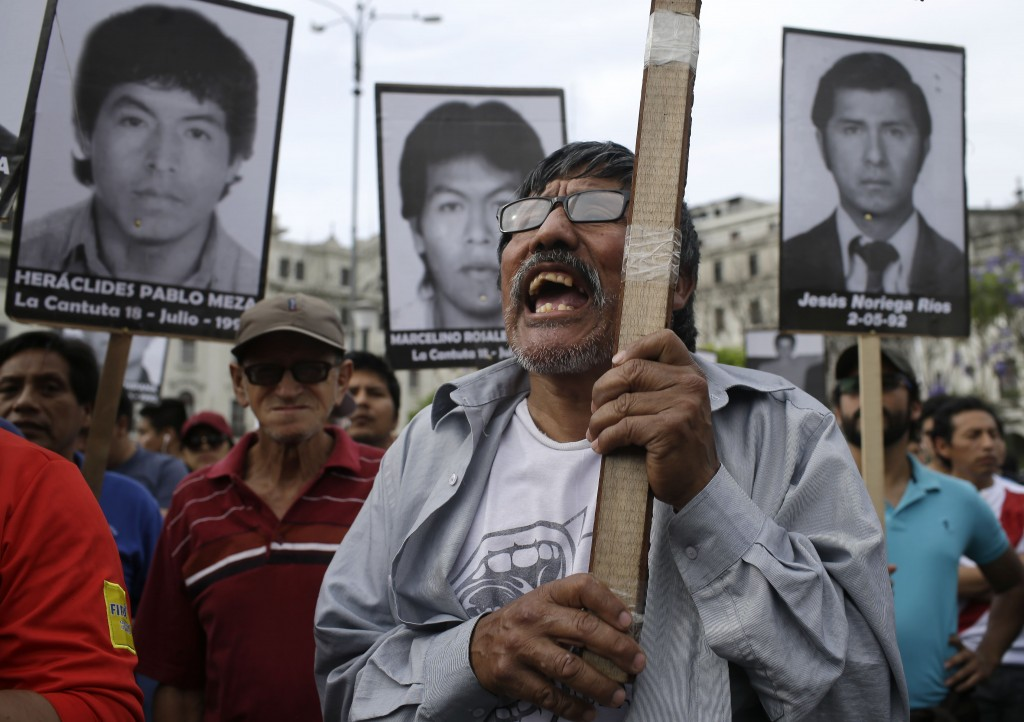 A demonstrators shouts slogans against pardon of former President Alberto Fujimori with photographs of the nine university students who were kidnapped...