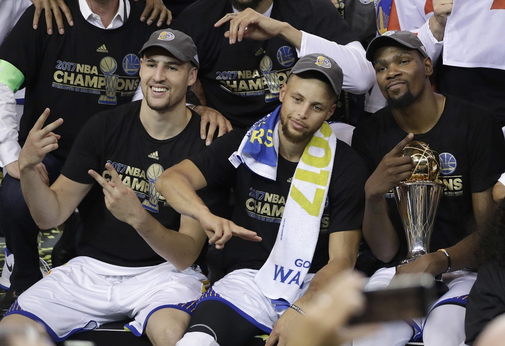 FILE - In this June 12, 2017, file photo, Golden State Warriors guard Klay Thompson, from left, guard Stephen Curry and forward Kevin Durant celebrate...