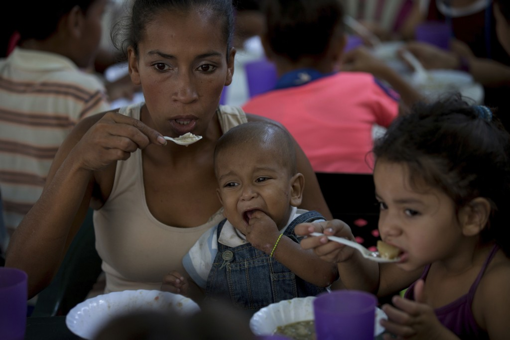 In this Dec. 12, 2017 photo, a mother with her son eat a free meal at a soup kitchen sponsored by the opposition in Caracas, Venezuela. The opposition...