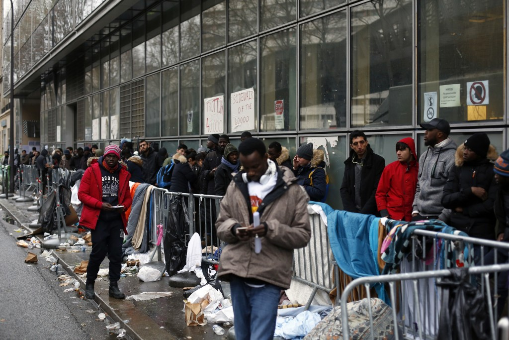Migrants queue outside a facility to apply for asylum, in Paris, Thursday, Dec. 21, 2017. The French government is scrambling to meet President Emmanu...
