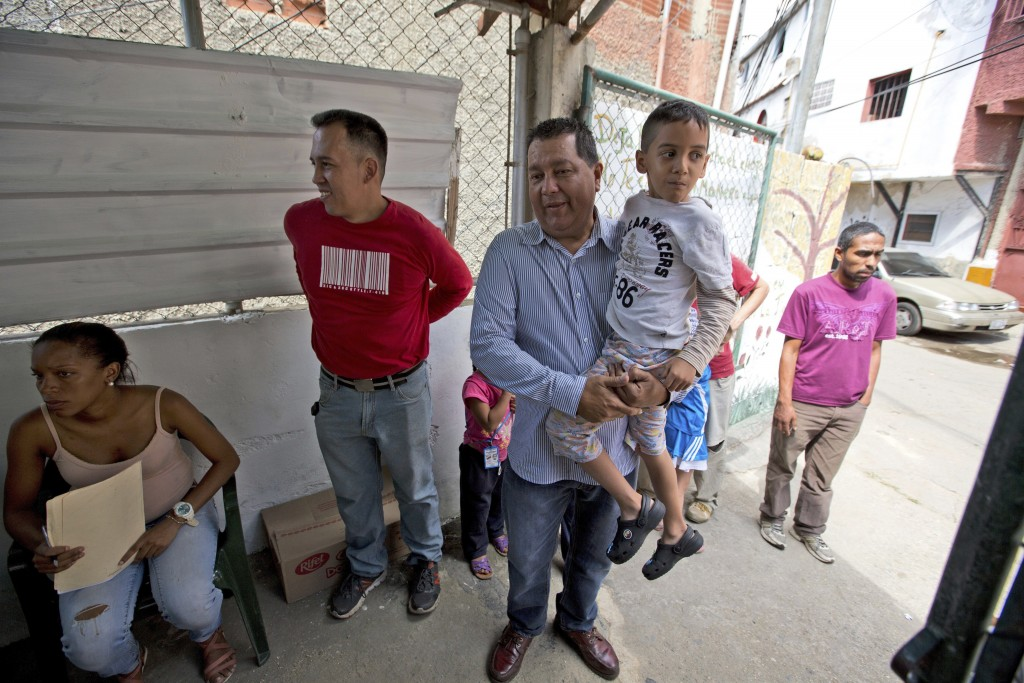 In this Dec. 12, 2017 photo, opposition politician Miguel Castillo holds a 6-year-old disabled boy named Tomas outside a soup kitchen sponsored by the...
