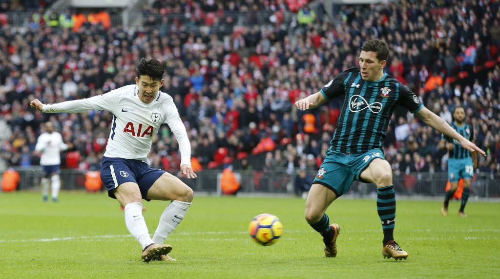 Tottenham Hotspur's Son Heung-min, left shoots and scores his sides 4th goal of the game during their English Premier League soccer match between Tott...