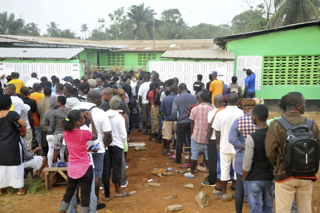 People wait to cast their votes during a Presidential runoff election in Monrovia, Liberia, Tuesday, Dec. 26, 2017. Young Liberians went straight from...