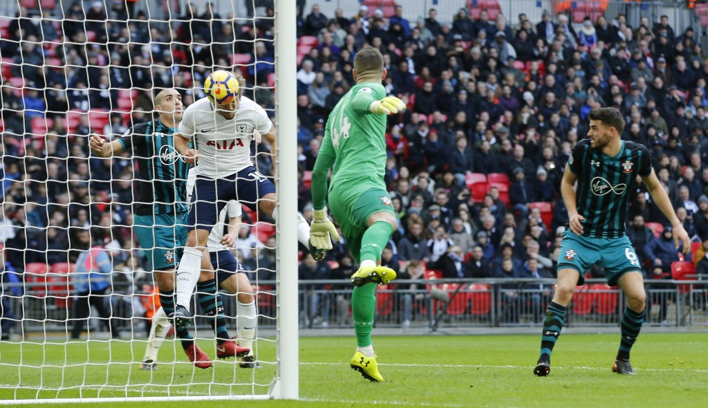 Tottenham Hotspur's Harry Kane, heads the ball to score the opening goal of the game during their English Premier League soccer match between Tottenha...