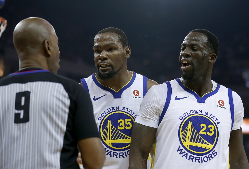 Golden State Warriors forward Kevin Durant (35) and forward Draymond Green (23) argue a call with referee Derrick Stafford (9) during the first half a...