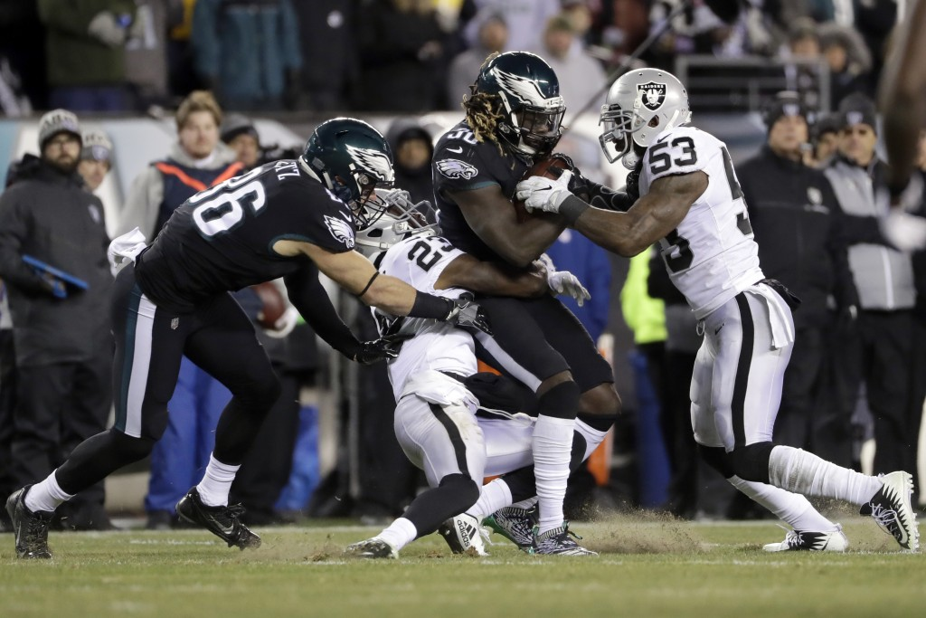 Philadelphia Eagles' Jay Ajayi (36) is tackled by Oakland Raiders' NaVorro Bowman (53) and Dexter McDonald (23) as Zach Ertz (86) defends during the f...
