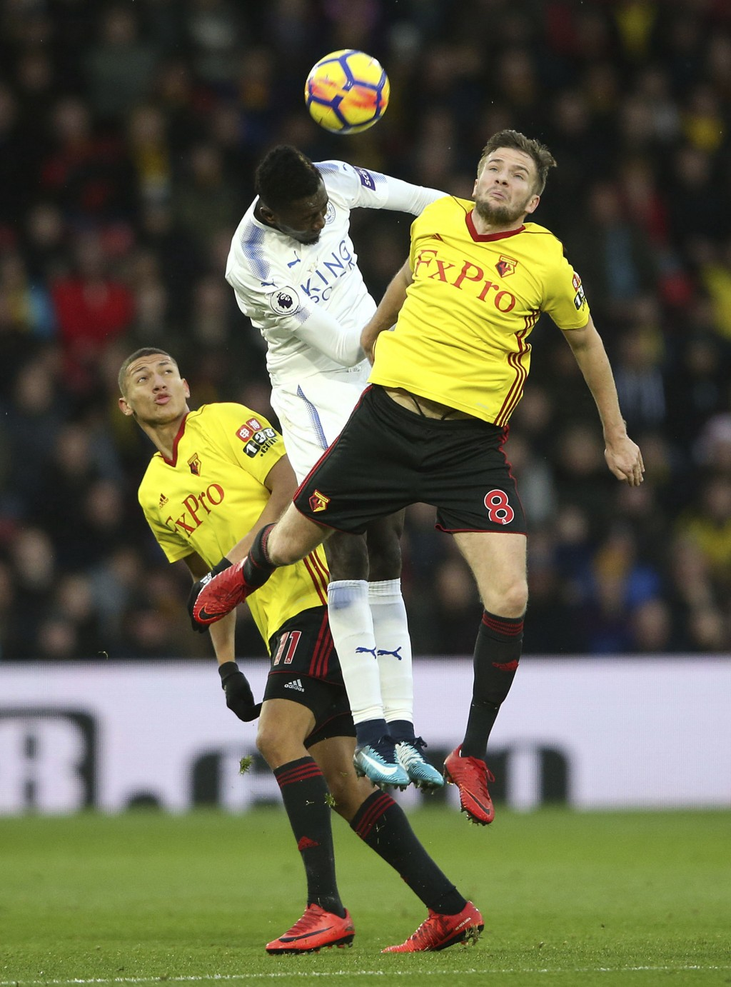 Leicester City's Wilfred Ndidi, centre, and Watford's Tom Cleverley, right, battle for the ball during the English Premier League soccer match at Vica...