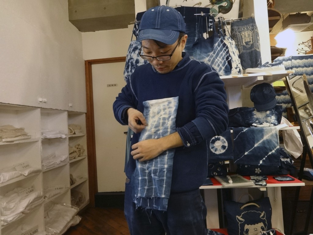 This Nov. 14, 2017 photo shows an instructor demonstrating a folding technique for designing indigo dyed fabric at Wanariya workshop in Tokyo. (Linda ...