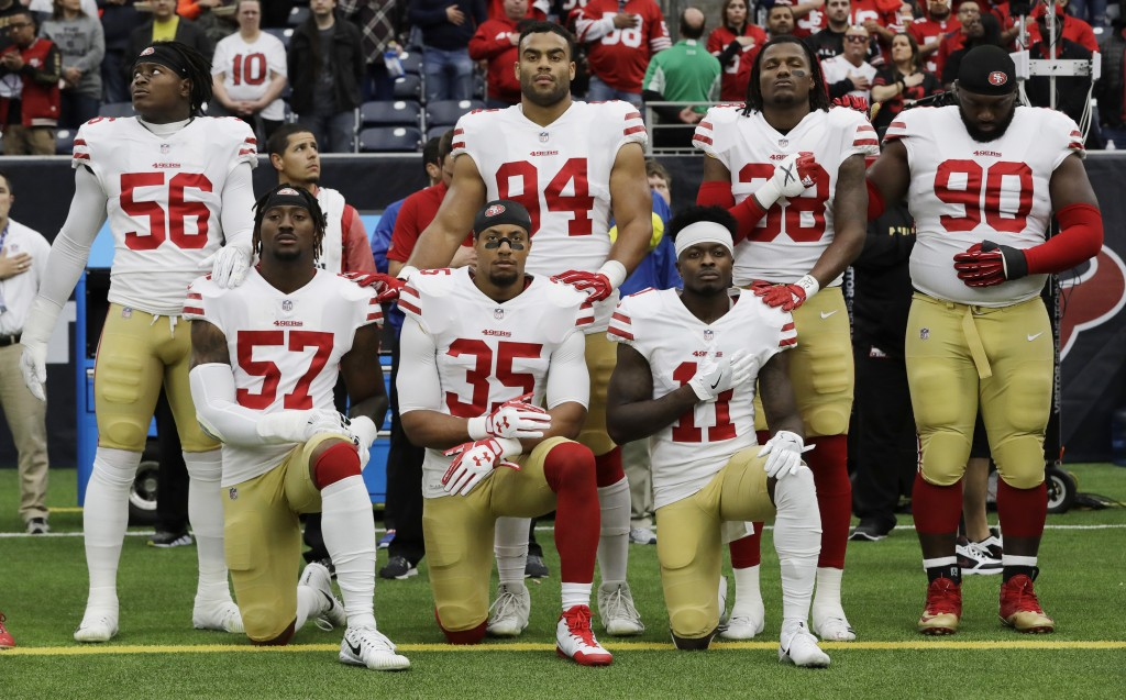 FILE - In this Dec. 10, 2017, file photo, San Francisco 49ers San Francisco 49ers' Eli Harold (57), Eric Reid (35) and Marquise Goodwin (11) kneel dur...