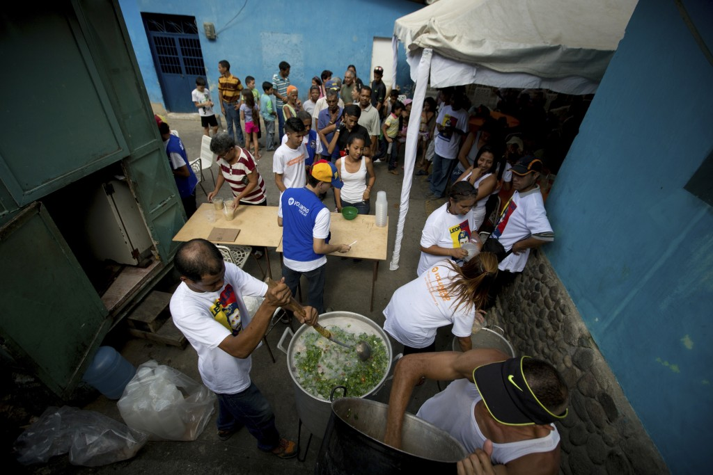 In this Dec. 9, 2017 photo, volunteers cook free soup for residents during a free medical care campaign for the poor people in La Guaira, Venezuela. A...