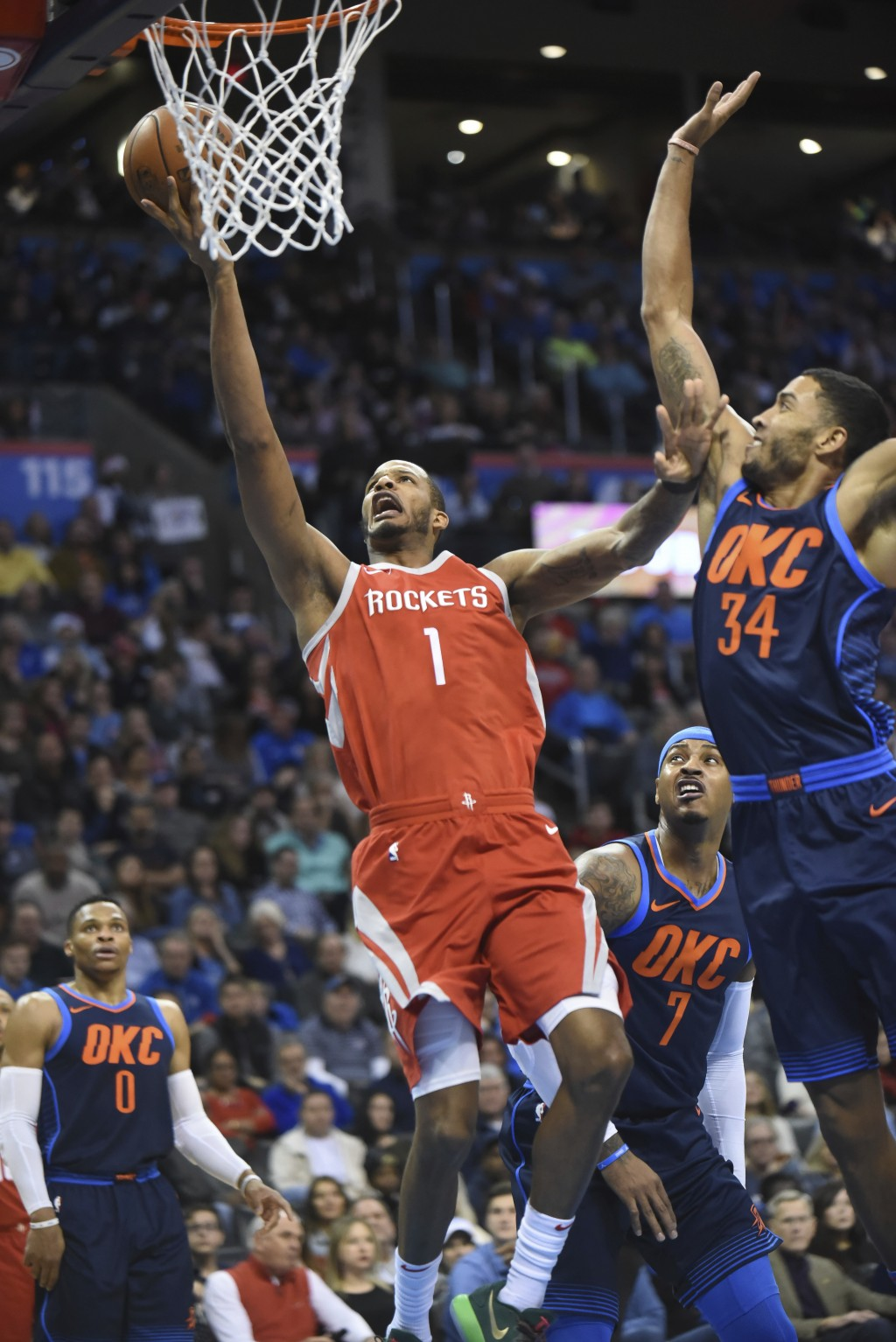 Houston Rockets' Trevor Ariza (1) shoots the ball around Oklahoma City Thunders' Josh Heustis (34) in the first quarter of an NBA basketball game in O...