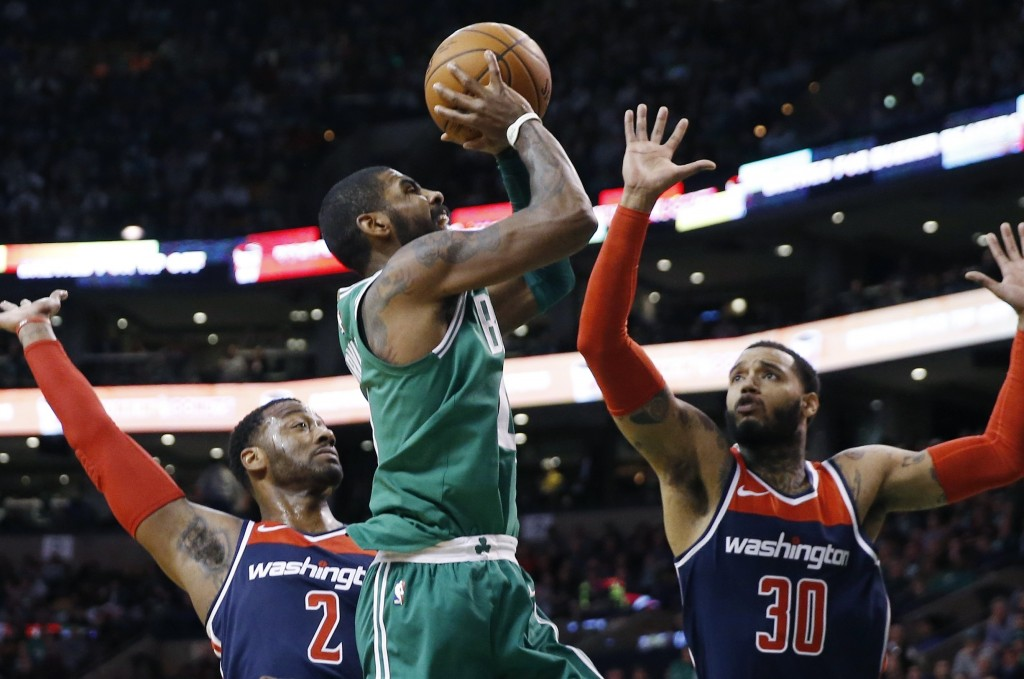 Boston Celtics' Kyrie Irving, center, shoots between Washington Wizards' John Wall (2) and Mike Scott (30) during the first quarter of an NBA basketba...