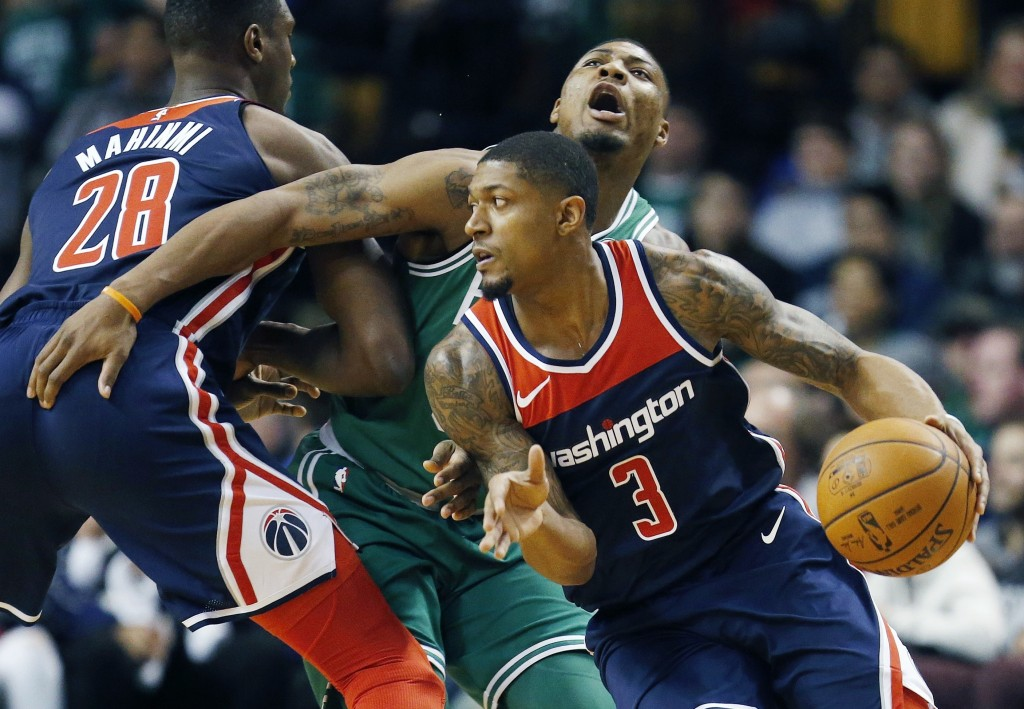 Washington Wizards' Bradley Beal (3) drives past Boston Celtics' Marcus Smart, behind, during the first quarter of an NBA basketball game in Boston, M...