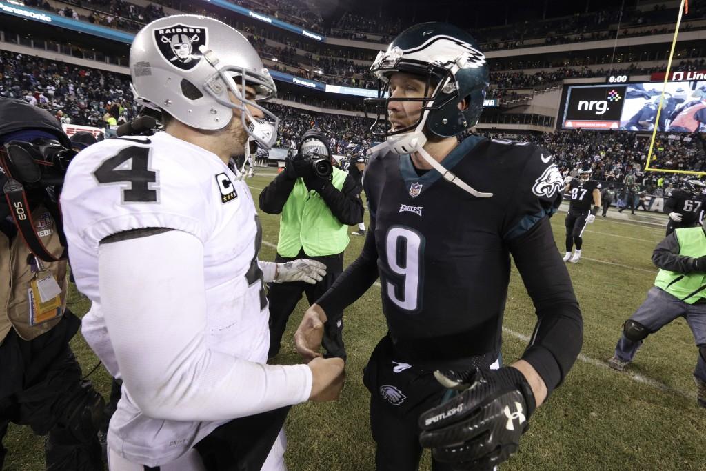 Philadelphia Eagles' Nick Foles (9) and Oakland Raiders' Derek Carr (4) meet after an NFL football game, Monday, Dec. 25, 2017, in Philadelphia. Phila...