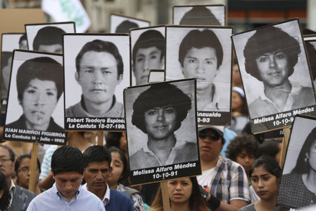 Demonstrators shouts slogans against pardon of former President Alberto Fujimori with photographs of people disappeared during his government, in Lima...