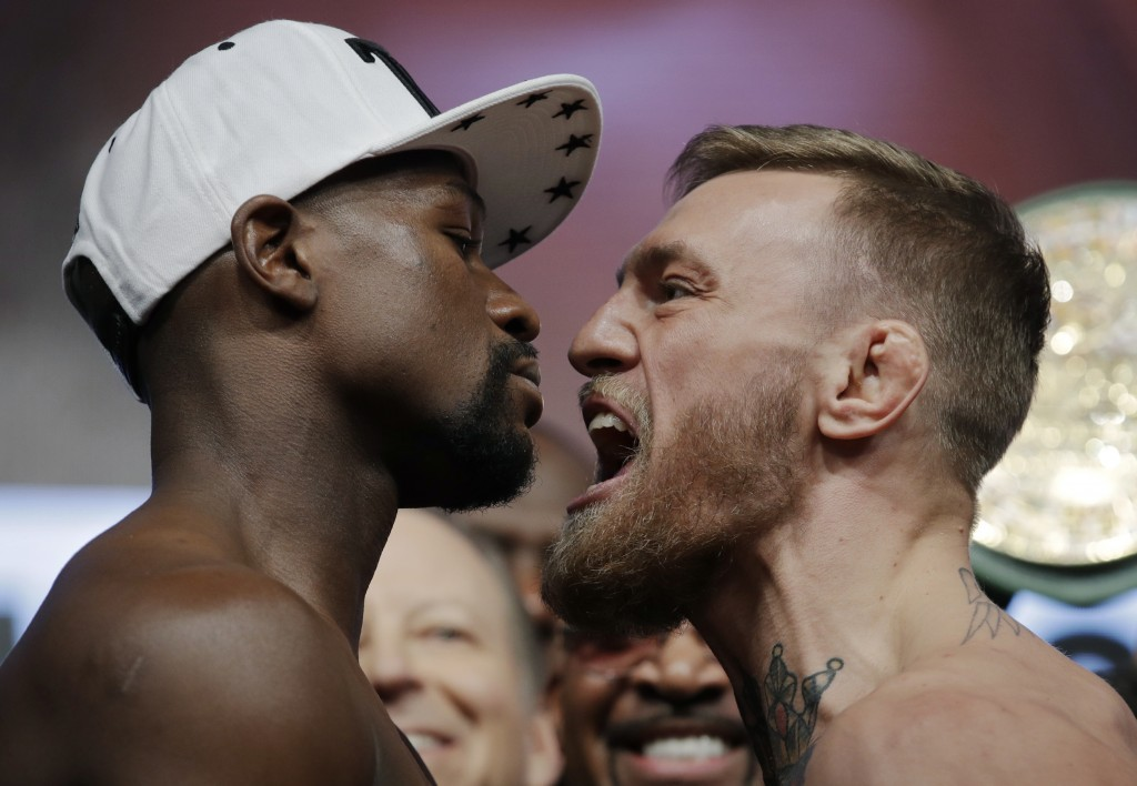 FILE - In this Friday, Aug. 25, 2017, file photo, Floyd Mayweather Jr., left, and Conor McGregor face off during a weigh-in in Las Vegas. McGregor ste...