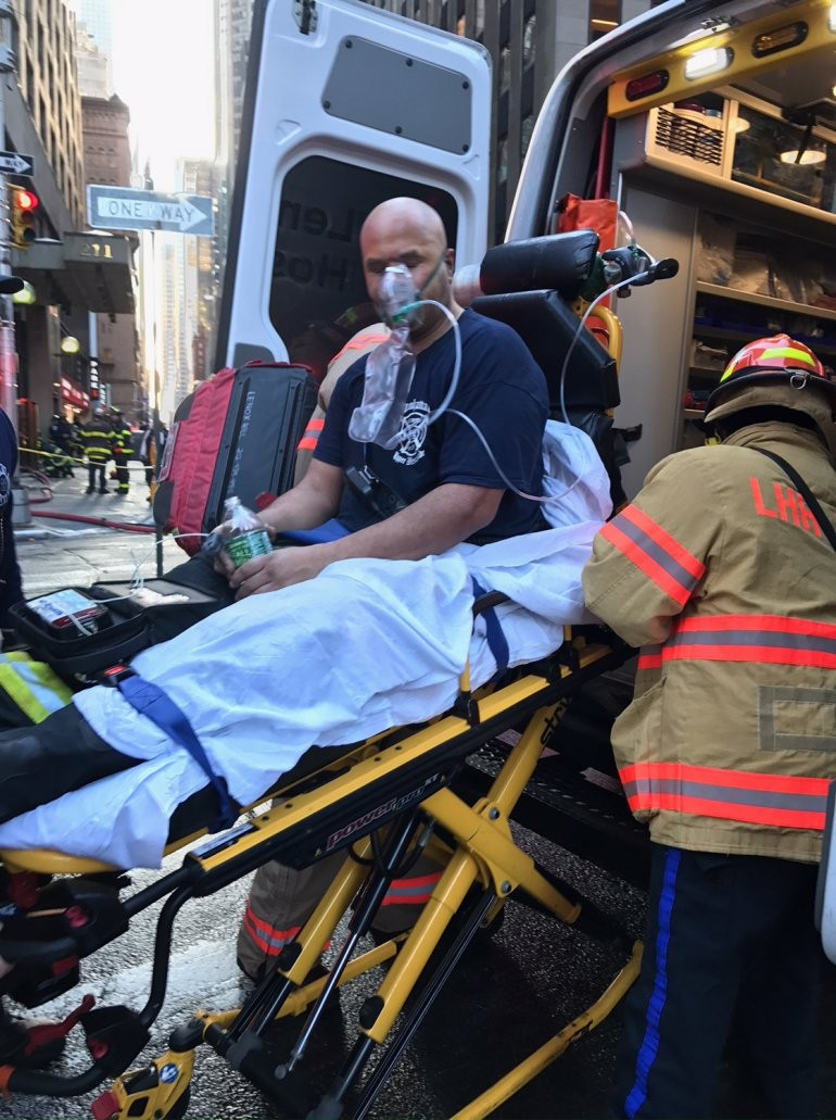 In this photo provided by WPIX-TV, one of two firefighters injured battling a wind-whipped Manhattan high-rise building fire that he New York Police D