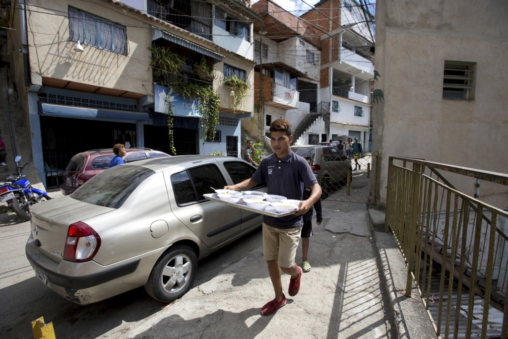 In this Dec. 12, 2017 photo, a volunteer brings a tray of food to serve to residents at a soup kitchen sponsored by the opposition in Caracas, Venezue...