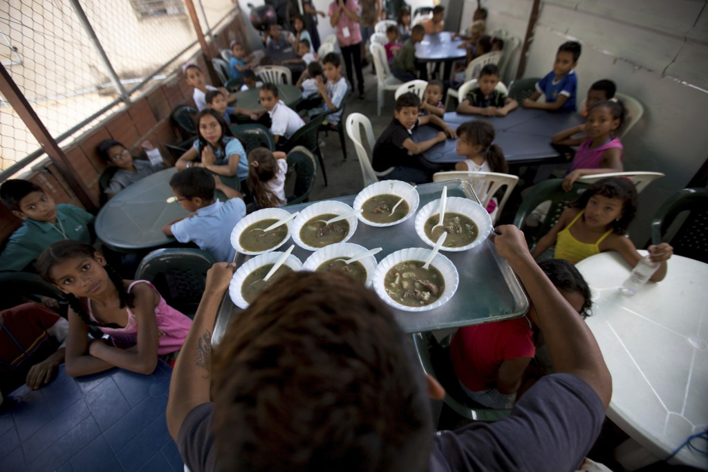 In this Dec. 12, 2017 photo, children watch their free meal arrive to be served at a soup kitchen sponsored by the opposition in Caracas, Venezuela. V...