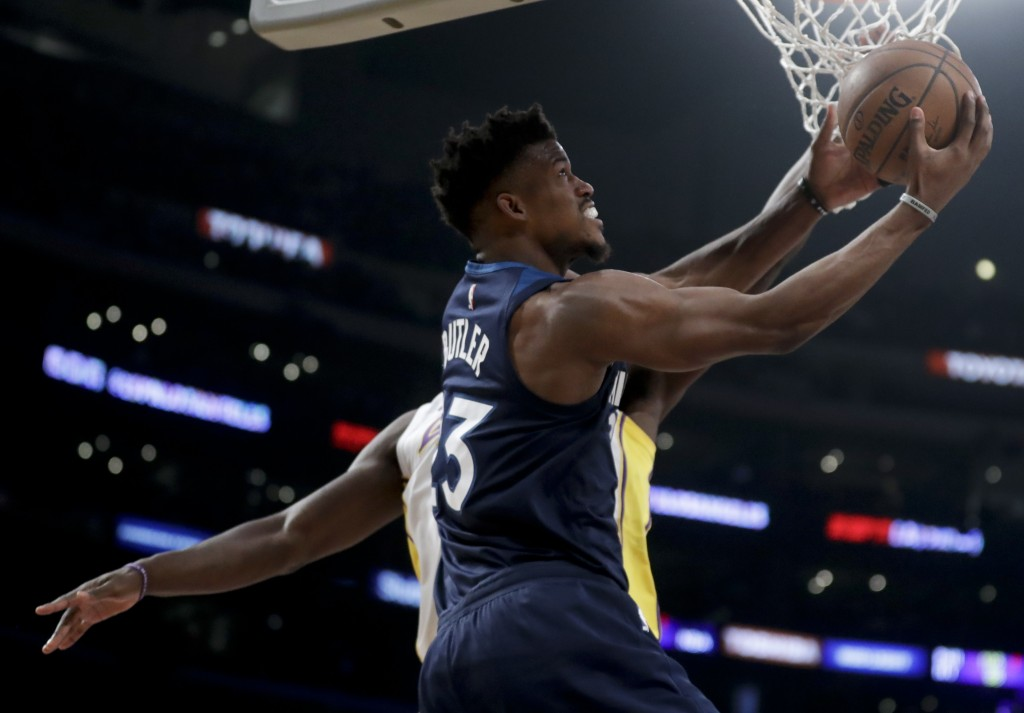 Minnesota Timberwolves guard Jimmy Butler (23) shoots around Los Angeles Lakers forward Julius Randle during the first half of an NBA basketball game ...