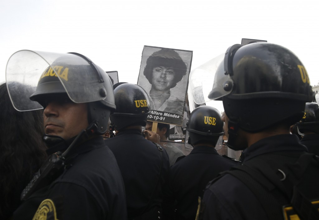 Demonstrators shout slogans against a medical pardon to former President Alberto Fujimori with photographs of people slain during his decade in power,...